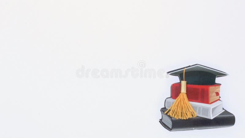 Avläggande av examenlock och bunt av böcker på vit bakgrund arkivbild