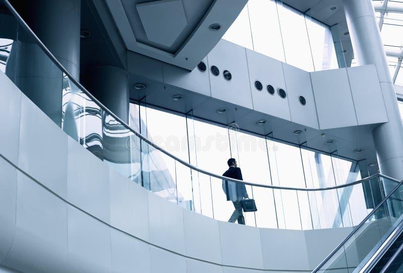 Avlägsen affärsman som går i en modern kontorsbyggnad arkivfoton