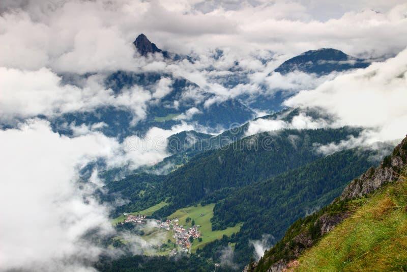 Avlägsen alpin by och mörker - gröna skogCarnic fjällängar Italien arkivbilder