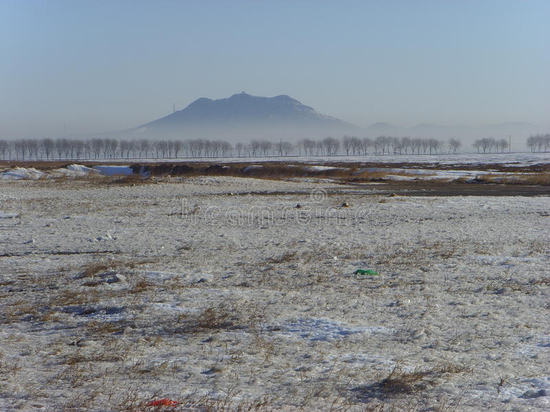 Avlägsen blick in i avståndskinesen Xingcheng Shoushan, efter snön royaltyfri foto