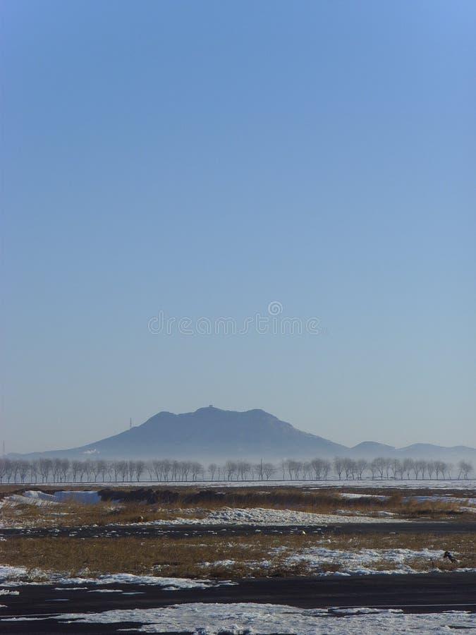Avlägsen blick in i avståndskinesen Xingcheng Shoushan, efter snön royaltyfri fotografi