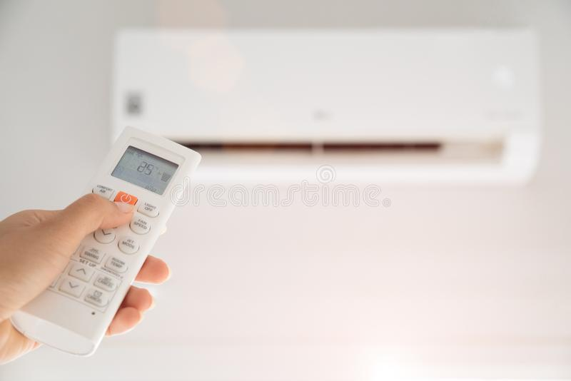 Avlägsen kontrollant för kvinnahandinnehav som riktas på luftkonditioneringsapparaten inom rummet och uppsättning på den omgivand royaltyfria foton