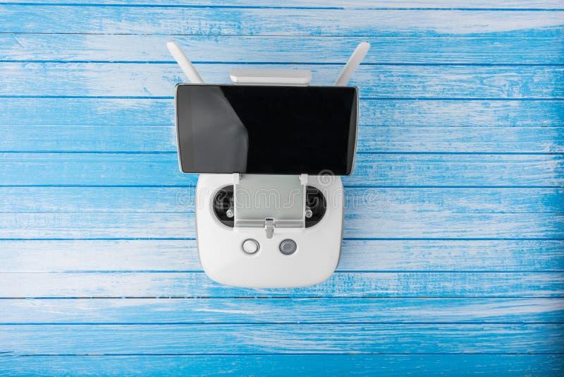 Avlägsen kontrollant With Smart Phone för modernt tekniskt avancerat vitt surr royaltyfria bilder