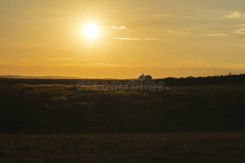 Avlägsen kyrka för solnedgånglandskap royaltyfria bilder