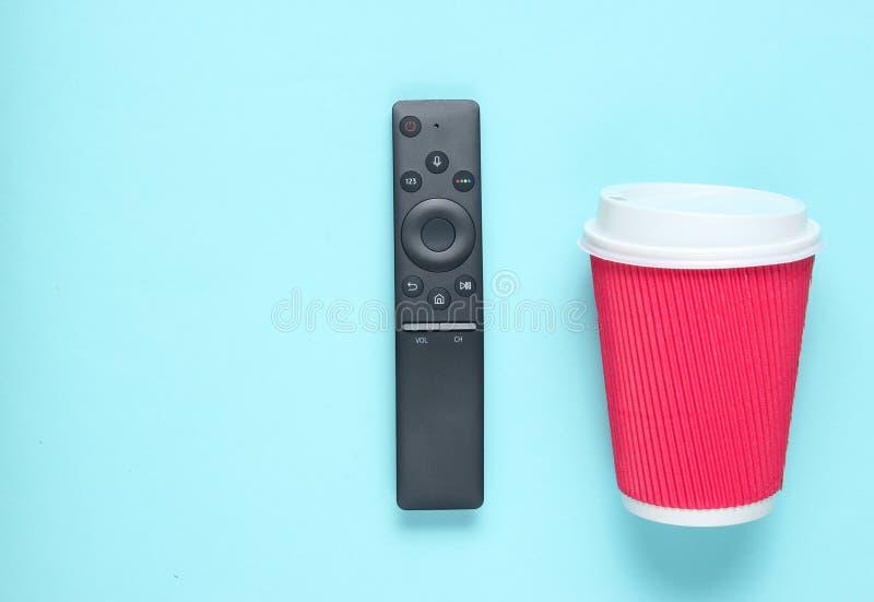 Avlägsen modern TV och pappers- kopp kaffe på blå pastellfärgad bakgrund Bästa sikt, minimalism royaltyfria bilder