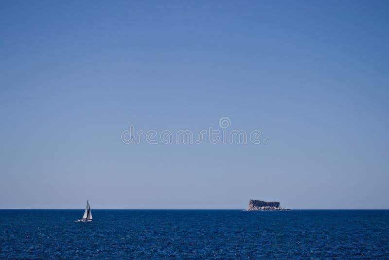 Avlägsen skeppsegling över mörkt - blått hav in mot den lilla steniga ön arkivfoto
