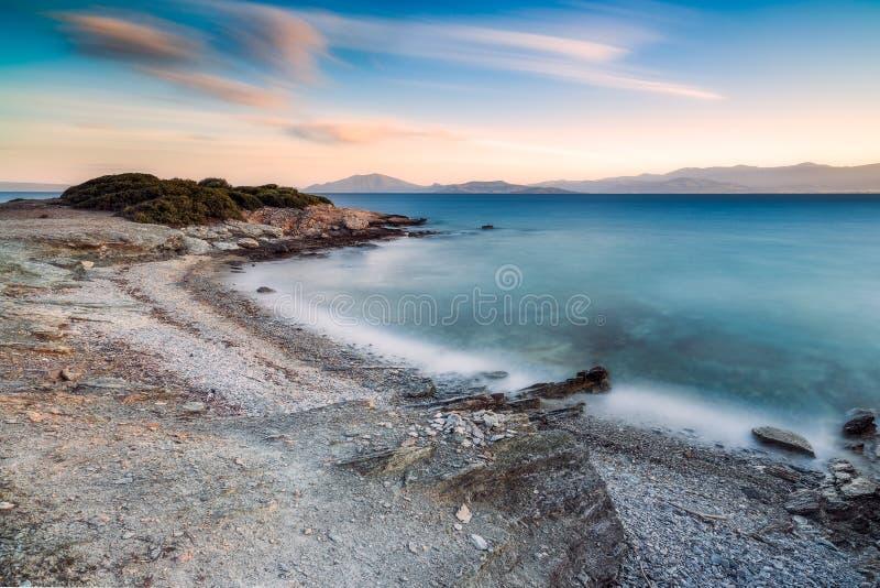 Avlägsen strand på solnedgången i Grekland royaltyfri bild