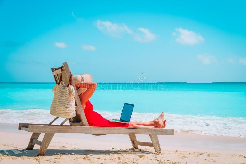 Avlägset arbetsbegrepp - ung kvinna med bärbara datorn på stranden arkivbilder