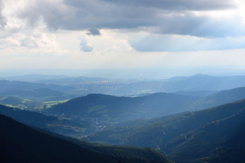 Avlägsna skogar och berg med solskenstrålar royaltyfri bild
