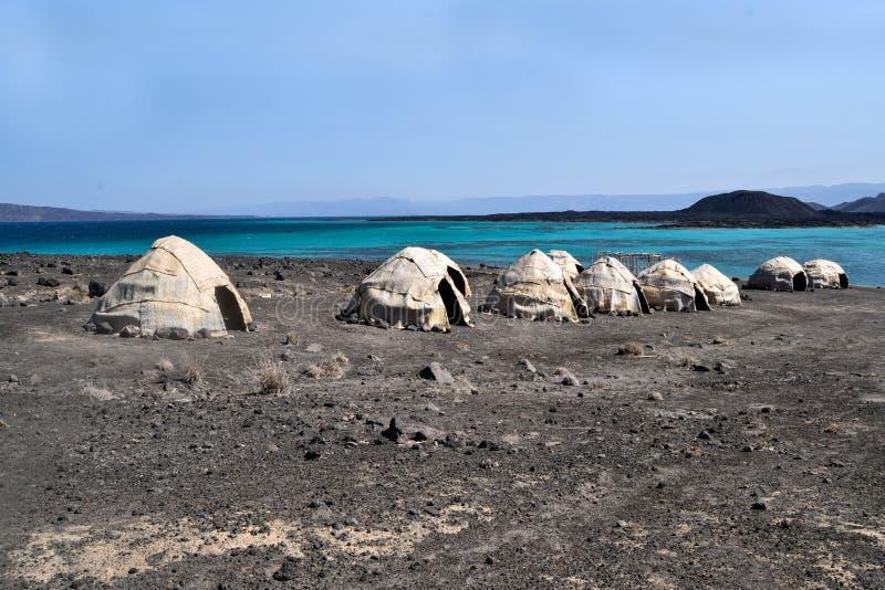 Avlägsna tält/kojaGhoubet strand, jäkelö Ghoubbet-el-Kharab Djibouti East Africa arkivfoton
