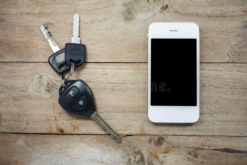 Avlägsna tangenter för mobiltelefon och för bil på trä royaltyfria bilder