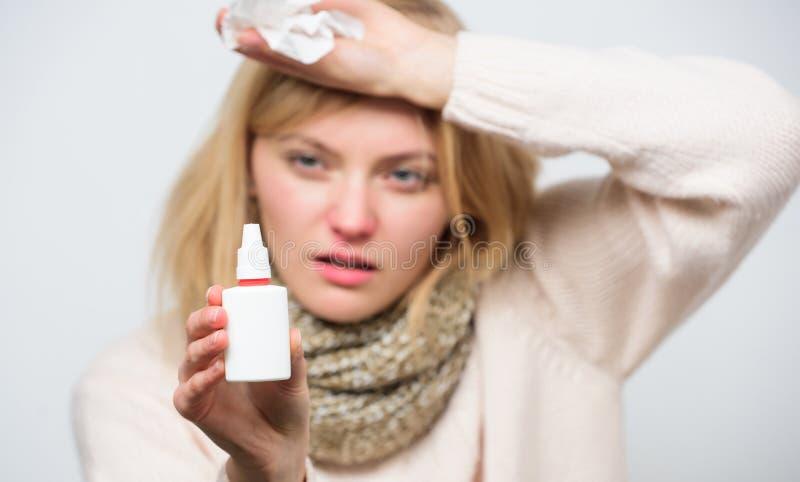 Avlösning av allergitecken Sjuklig flicka med den rinnande näsan genom att använda nasal sprej Sjuk kvinna som besprutar läkarbeh royaltyfri foto