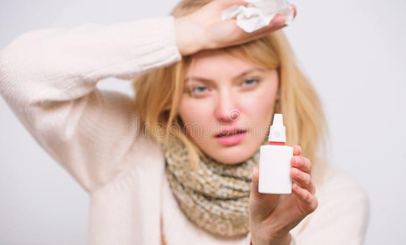 Avl?sning av allergitecken Sjuklig flicka med den rinnande n?san genom att anv?nda nasal sprej Sjuk kvinna som besprutar l?karbeh royaltyfri bild