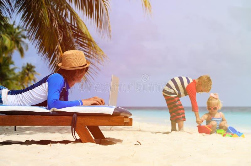 Avla arbete på bärbara datorn, medan ungar spelar på stranden fotografering för bildbyråer