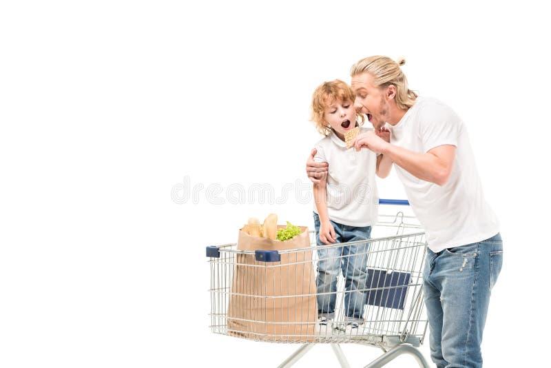 avla att äta kakan samman med son i shoppingvagn arkivfoto