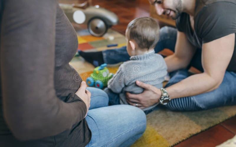 Avla att att bry sig sonen, medan gravida modersmekningar buktar arkivbilder