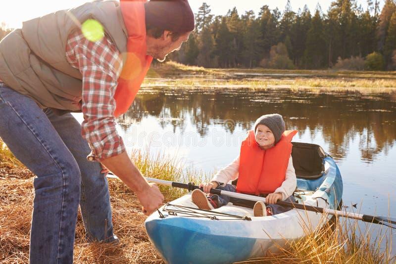 Avla att förbereda lanseringen för son i kajak på lakeside arkivfoto