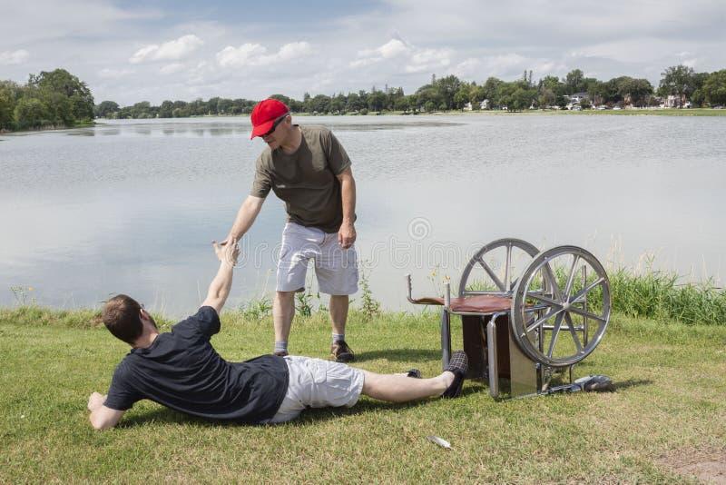 Avla att försöka att hjälpa sonen av jordningen, når du har fallit ut ur rullstolen royaltyfria foton
