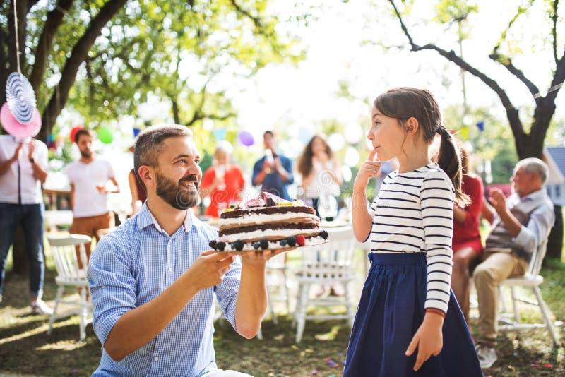 Avla att ge en kaka till en liten dotter på en familjberöm eller ett födelsedagparti royaltyfria bilder