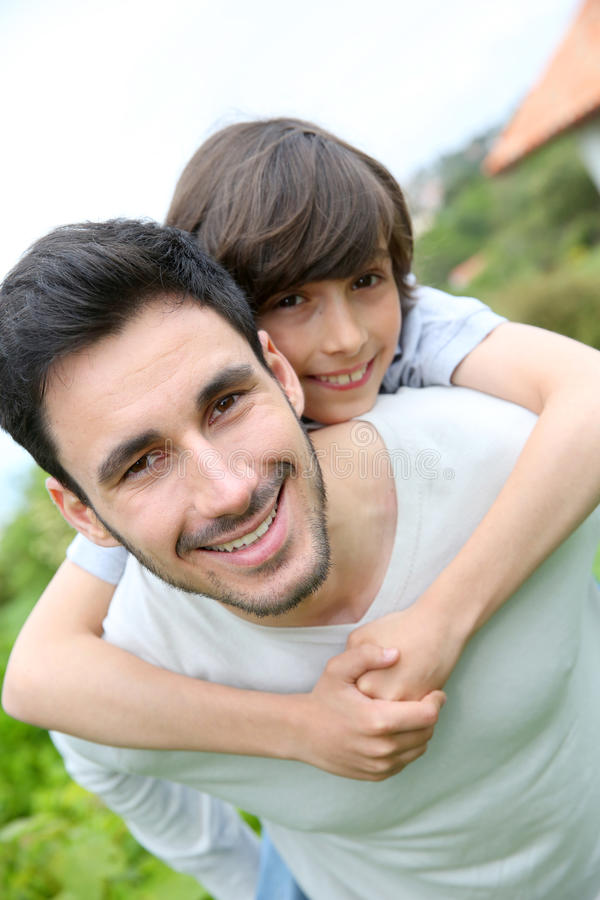 Avla att ge en ridtur på axlarnaritt till hans son utomhus arkivbild