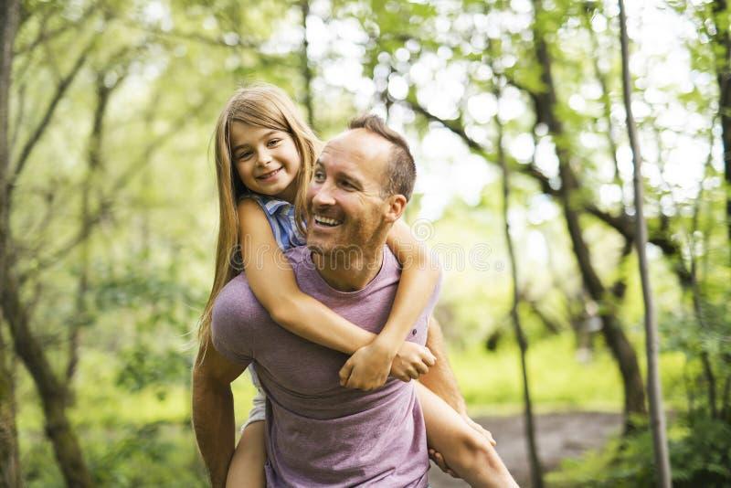 Avla att ge hans dotter en ridtur på axlarnaritt och att ha gyckel royaltyfri fotografi