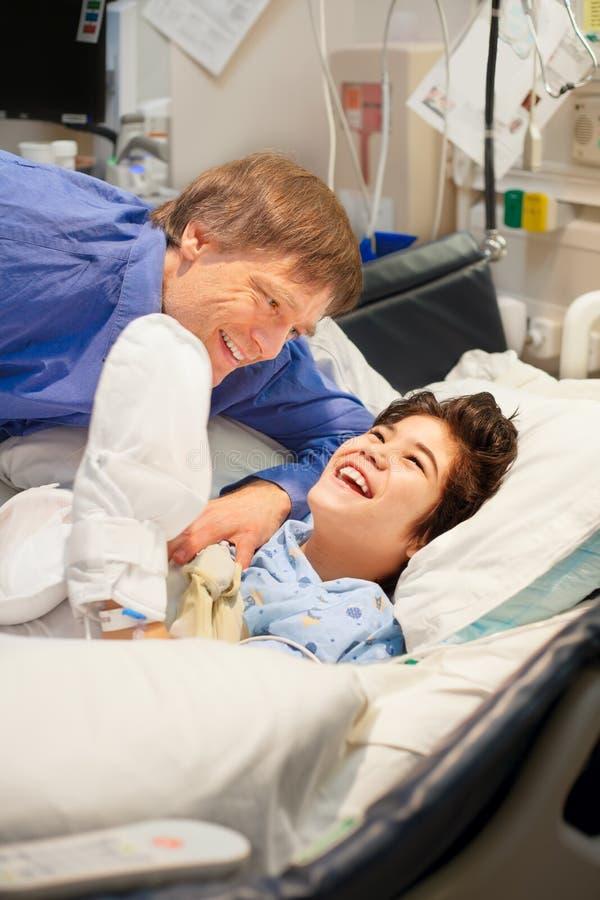 Avla att hålla ögonen på över rörelsehindrad son i sjukhussäng arkivfoton