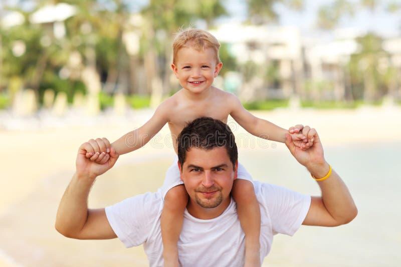 Avla att ha gyckel på stranden med hans lilla son royaltyfri foto