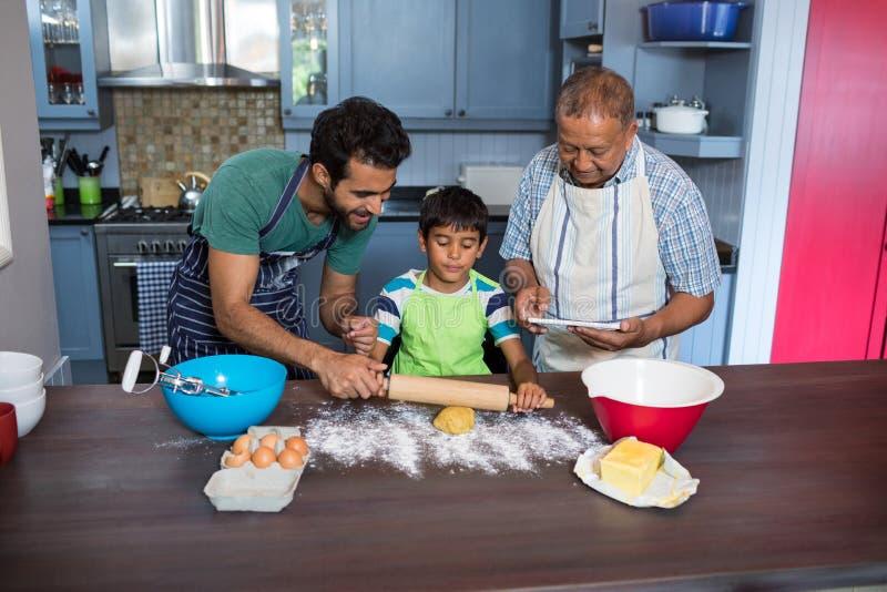 Avla att hjälpa sonen för att förbereda mat, medan stå av mannen som använder minnestavlan royaltyfria foton
