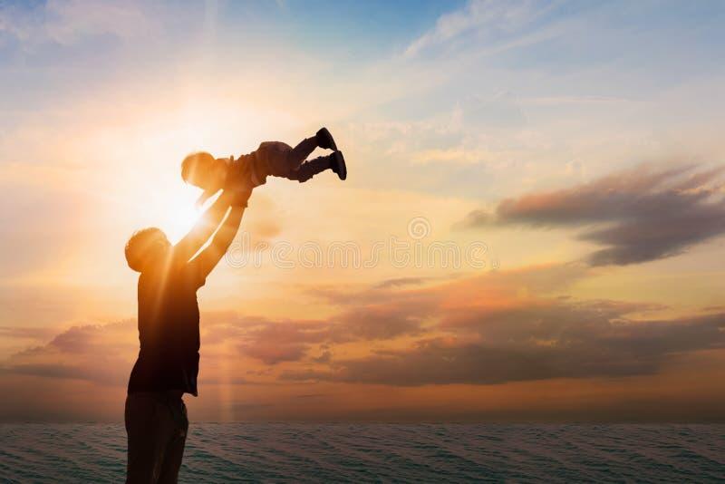 Avla att kasta hans son på stranden på solnedgångtiden Begrepp arkivbilder