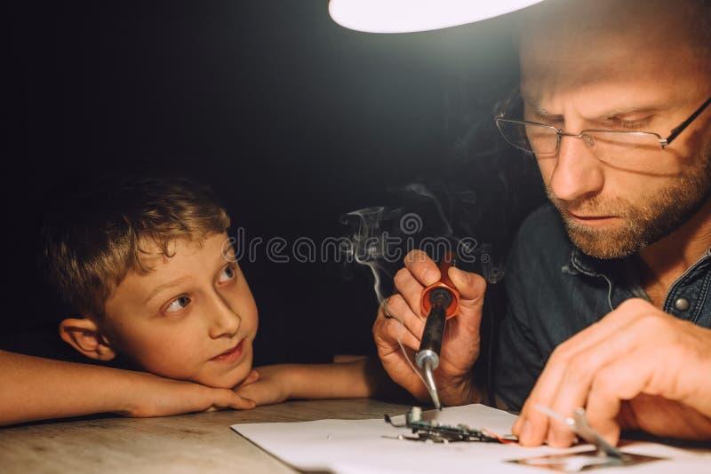 Avla att löda med elektrisk lödkolv och hans lilla son royaltyfri foto