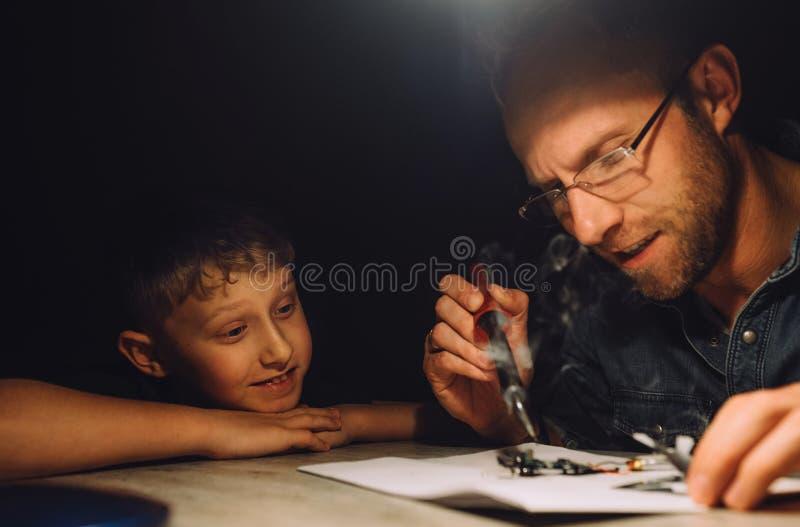 Avla att löda med elektrisk lödkolv och hans lilla son arkivbilder