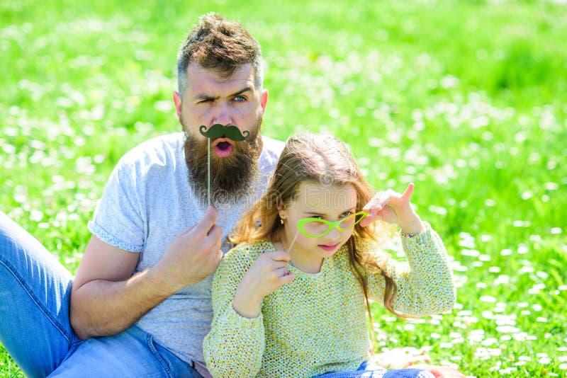 Avla att posera med mustaschen och barnet som poserar med attribut för glasögonfotobås Kriminalarebegrepp Farsa och dotter arkivbild
