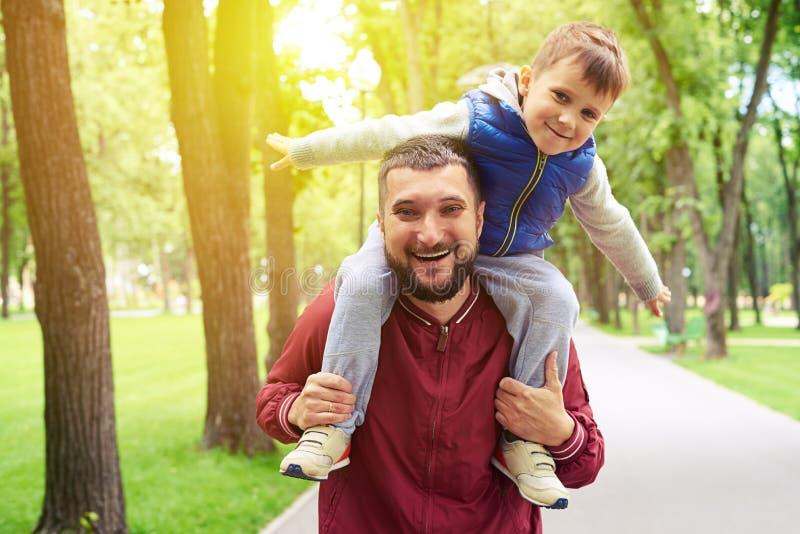 Avla att rida hans lilla son på skuldror parkerar in på solig dag royaltyfri fotografi