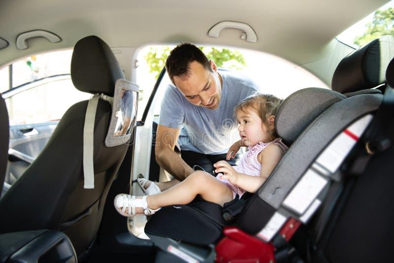 Avla att sätta hans barndotter in i hennes bilsäte i bilen arkivfoto
