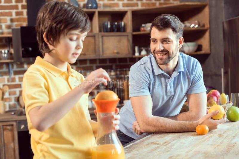 Avla att se den lilla sonen som pressar ny fruktsaft i kök fotografering för bildbyråer