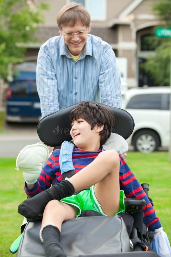 Avla att skjuta årig rörelsehindrad son tio i rullstol utomhus arkivfoton