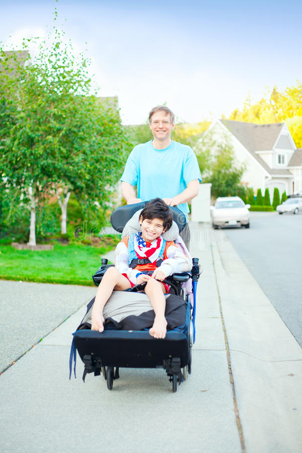 Avla att skjuta årig rörelsehindrad son tio i rullstol utomhus royaltyfria foton