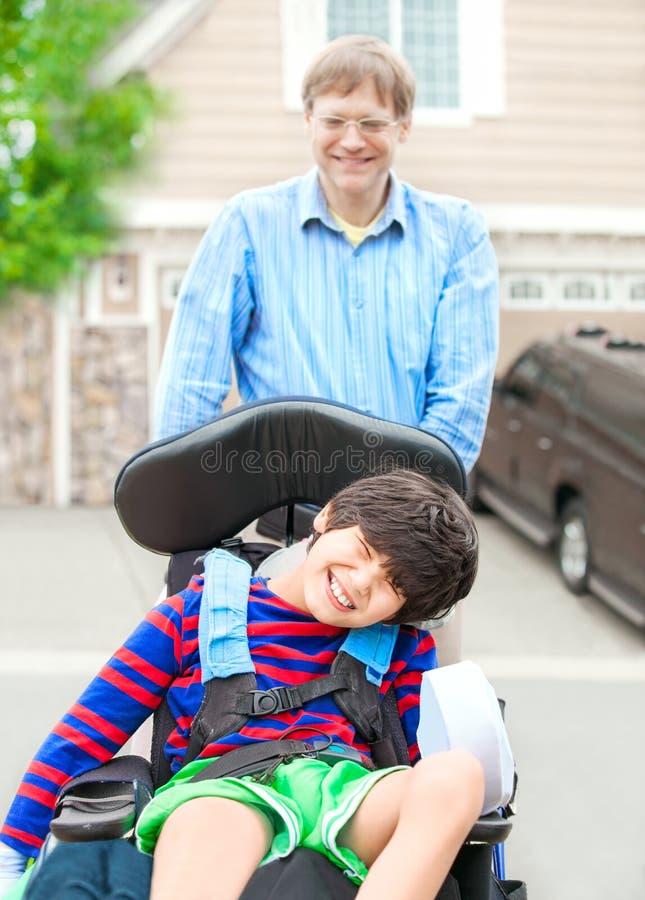 Avla att skjuta årig rörelsehindrad son tio i rullstol utomhus arkivbilder
