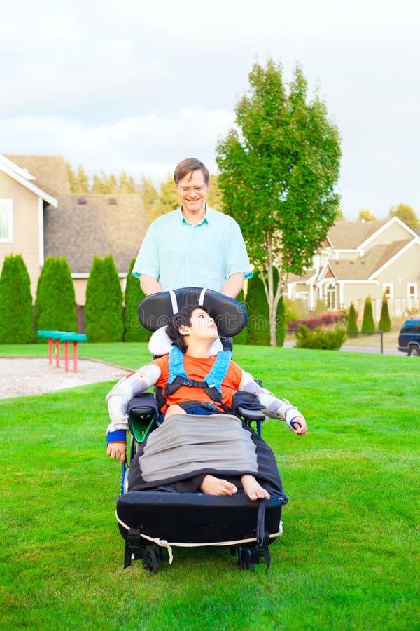 Avla att skjuta den rörelsehindrade sonen i rullstol på parkerar royaltyfria bilder