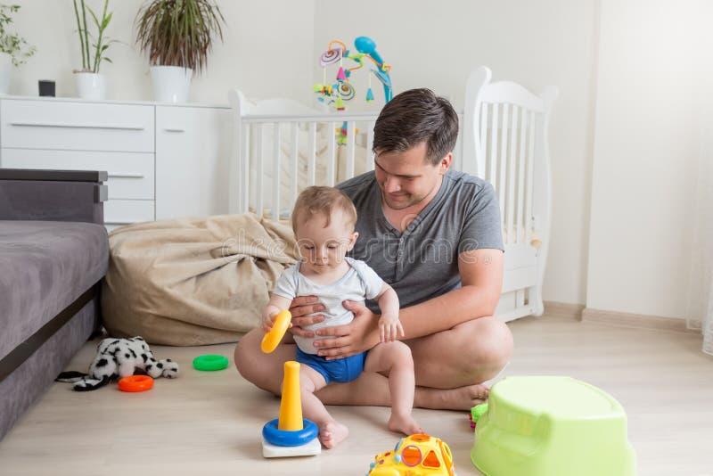 Avla att spela med hans 9 gamla månader behandla som ett barn pojken hemma arkivfoto