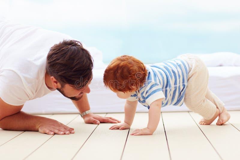Avla att spela med hans lilla son på golvet arkivbild