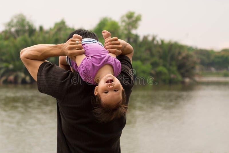 Avla att spela och att bära hans barn på hans skuldror nära en flod royaltyfri foto