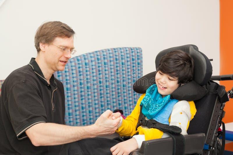 Avla att spela tummebrottning med den rörelsehindrade sonen i rullstol arkivbild
