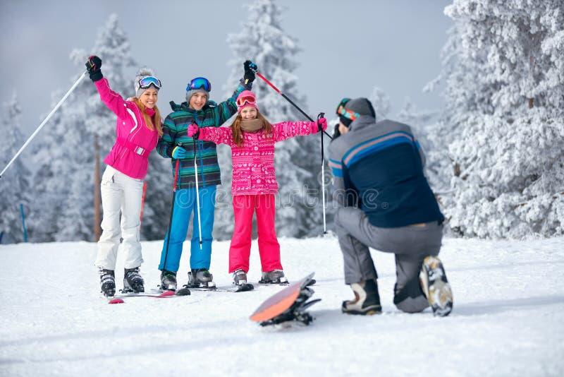 Avla att ta bilden av familjen skidar på ferie i berg royaltyfri bild