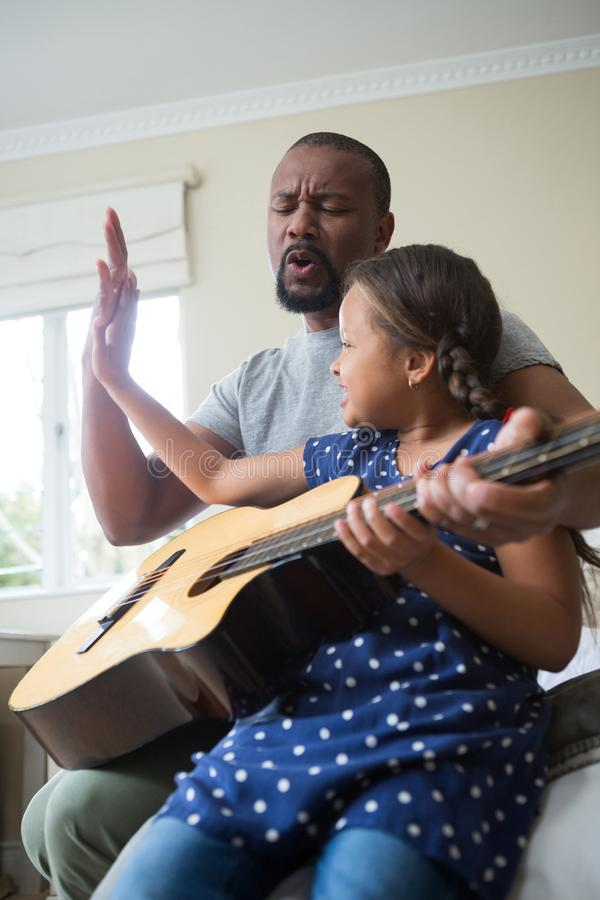 Avla att undervisa hans dotter att spela gitarren arkivfoto