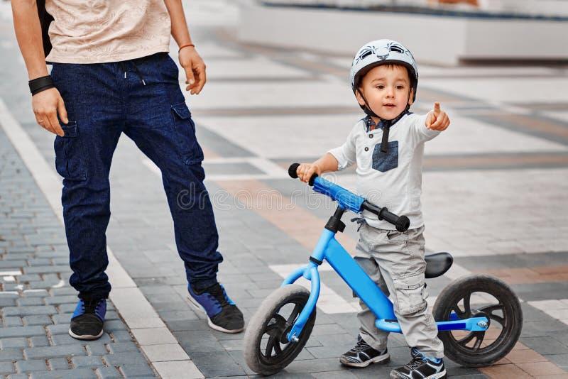Avla att undervisa hans son att rida en cykel arkivfoton