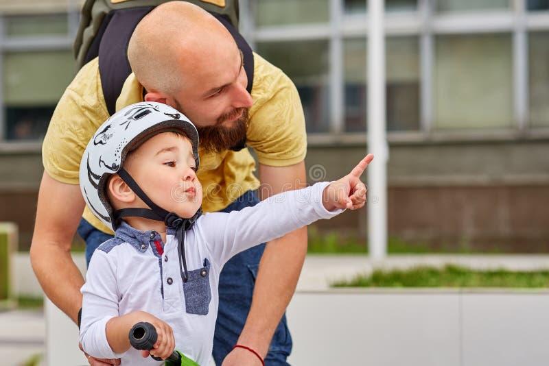 Avla att undervisa hans son att rida en cykel royaltyfria foton