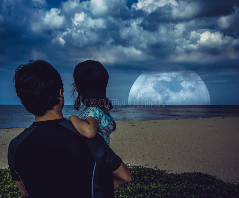 Avla den bärande dottern och att se den toppna månen över havet arkivbilder