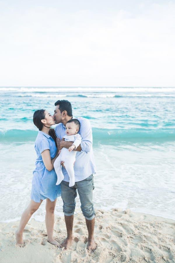 Avla den kyssande modern, medan rymma deras gulliga son arkivfoto