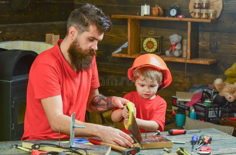 Avla föräldern med skägget som undervisar den lilla sonen till att såga med den skarpa handsawen, snickarehantverk Manligt arbets royaltyfri bild